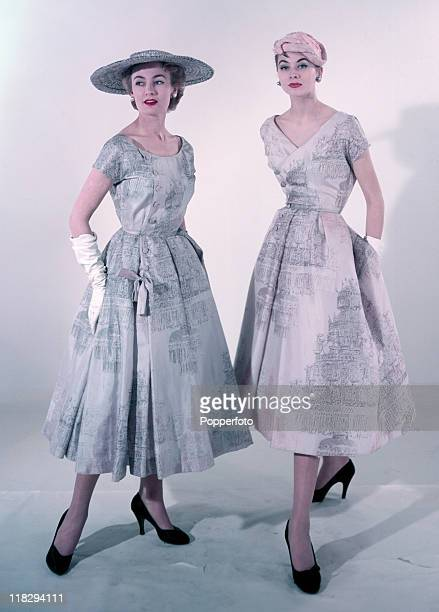Elegant pastelcoloured and patterned belowtheknee day dresses in light blue and mauve with matching hats worn by two models in a studio setting circa...