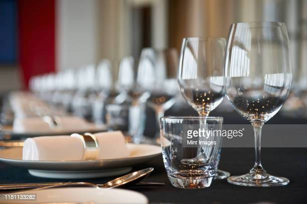 elegant place settings on a long table - banquet stock pictures, royalty-free photos & images