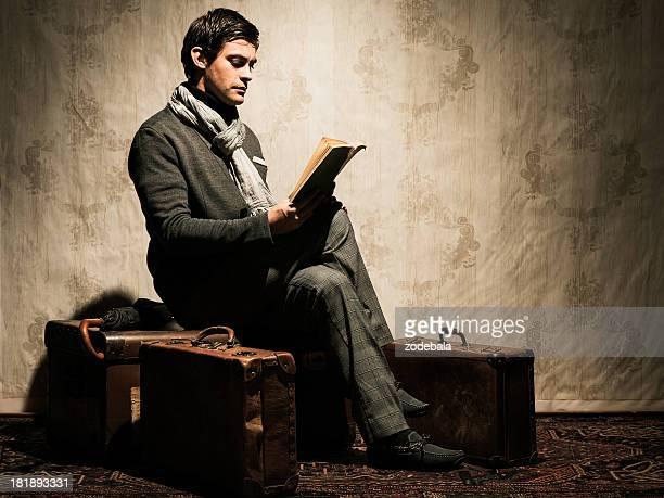 Elegant Retro Man Reading a Book among Travelling bags