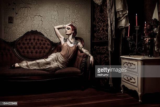 elegante retro frau entspannen auf dem sofa - barock stock-fotos und bilder