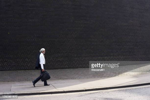 elegant senior businessman with luggage walking on pavement - elegance stock pictures, royalty-free photos & images