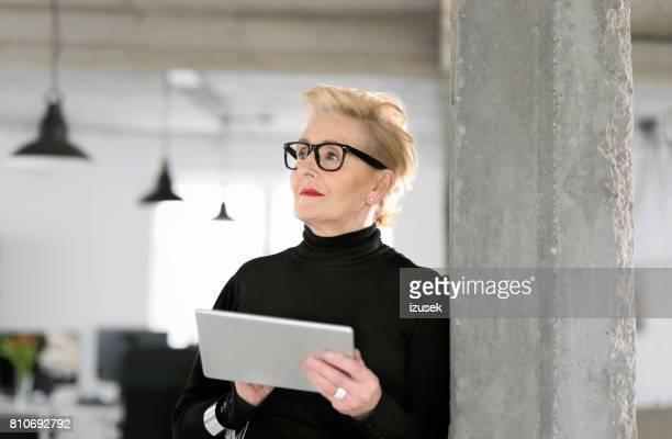 elegante senior geschäftsfrau, die mit einem digitalen tablet im studio - izusek stock-fotos und bilder