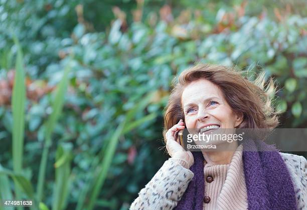 Elegant senior lady talking on the phone outdoors (London, UK)