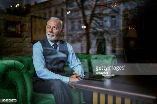 elegant senior man sitting on couch in a cafe looking out of window - baby boomer stock-fotos und bilder