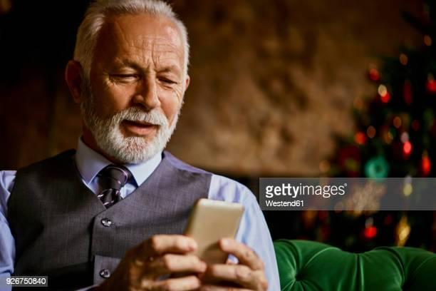 elegant senior man using cell phone - ereignis atmosphäre stock-fotos und bilder