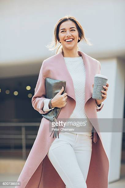 elegant smiling woman walking outdoors - fashionable stock photos and pictures