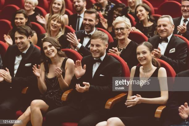 elegant spectators clapping in the theater - audience stock pictures, royalty-free photos & images