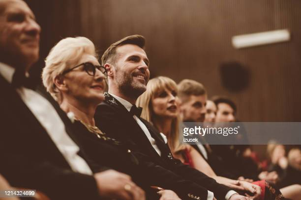 elegant spectators sitting in the theater, focus on senior woman - gala stock pictures, royalty-free photos & images