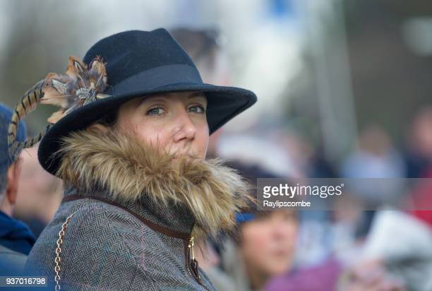 Elegant, stylish woman mingling with the large crowds on her way to the world famous Cheltenham Festival Horse Races