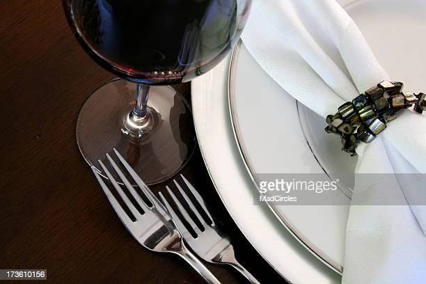 Elegant table setting with napkin ring and a glass of wine