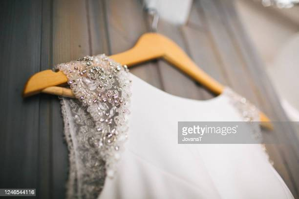 elegant wedding dress hanging on gray wall - wedding dress stock pictures, royalty-free photos & images