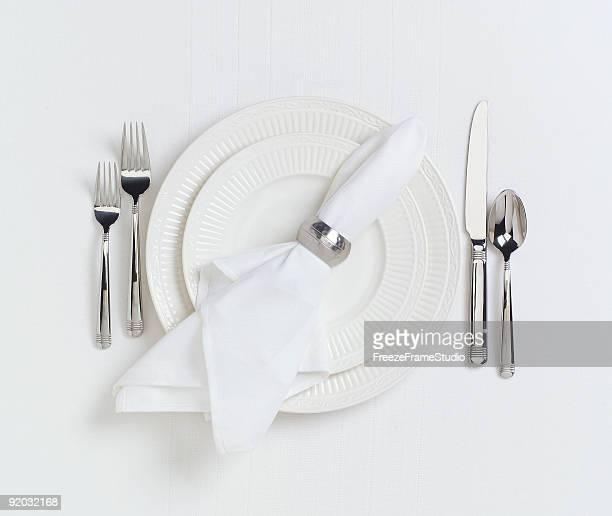 Elegant white dinner placesetting on white linen tablecloth