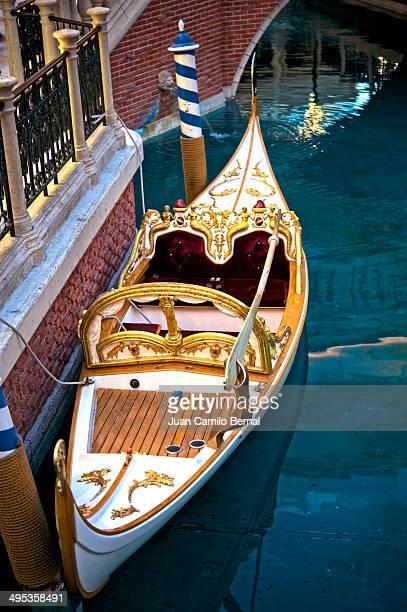 Elegant white gondola parked next to a brick wall