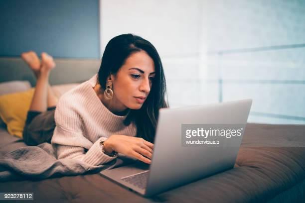 elegant woman browsing online using laptop while lying on bed - photo messaging stock pictures, royalty-free photos & images