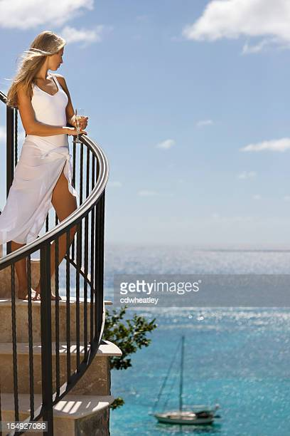 elegant woman enjoying a glass of champagne and Caribbean view