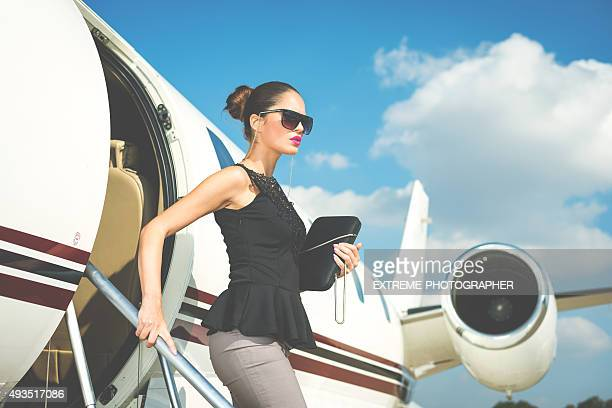 Elegant woman exiting private jet airplane