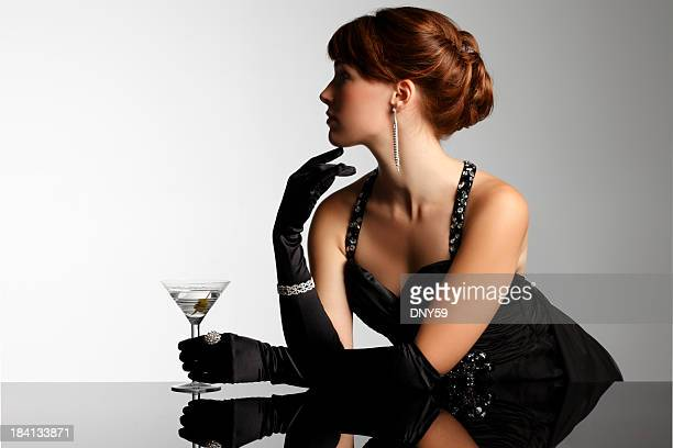 Elegant woman in black gloves holding martini