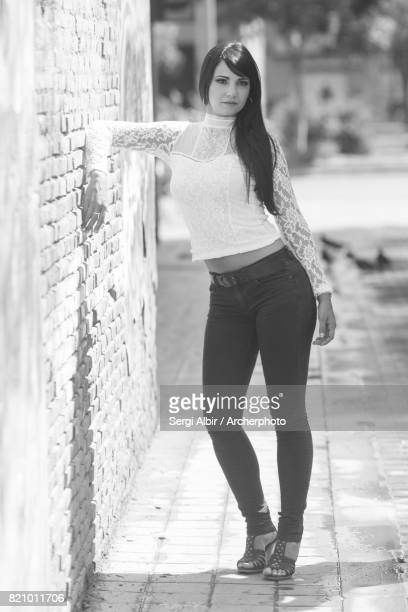 Elegant woman leaning against a wall in a Valencia street.