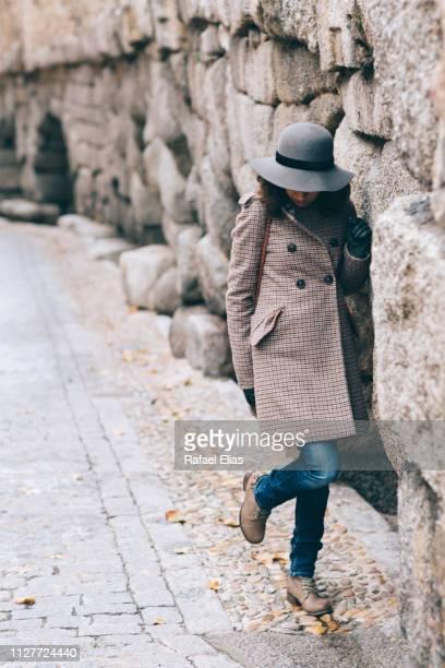 elegant woman looking down by stone wall - look down stock-fotos und bilder