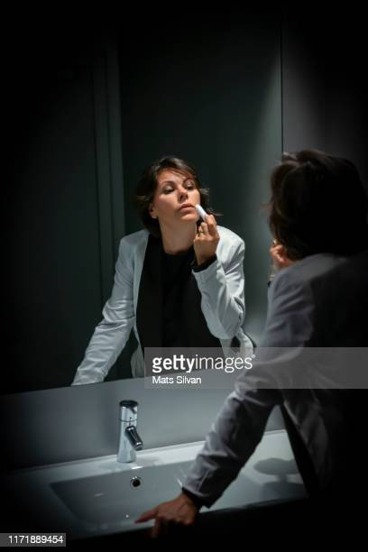 elegant woman looking in mirror and applying lipstick in bathroom - vanity mirror stock pictures, royalty-free photos & images