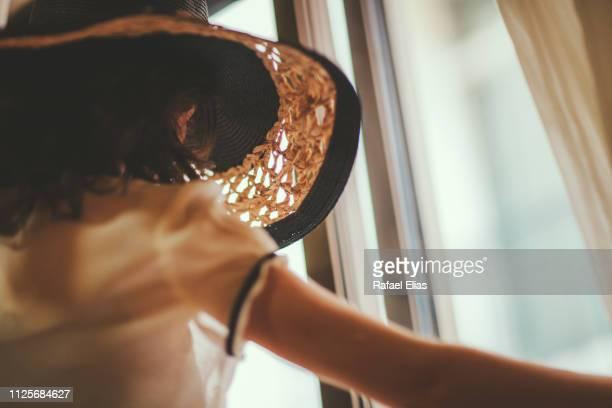 elegant woman looking through the window - open blouse - fotografias e filmes do acervo