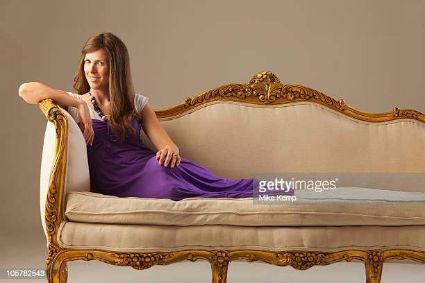 Elegant woman lounging on antique sofa