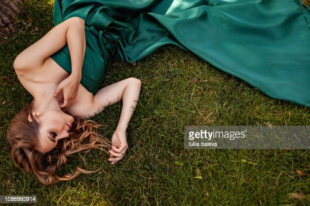 elegant woman lying on grass - evening gown stock pictures, royalty-free photos & images