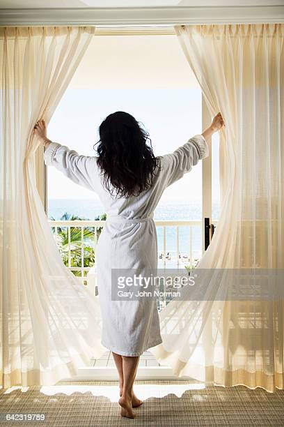 Elegant woman opens curtains in hotel