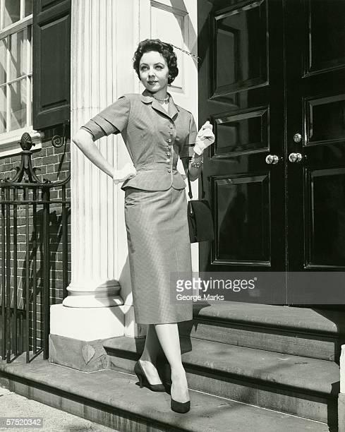 Elegant woman posing at entrance to building, (B&W), portrait