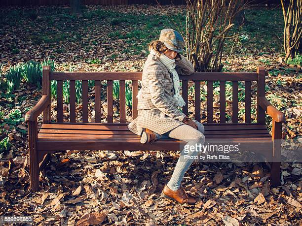 Elegant woman sitting on a bench at the park