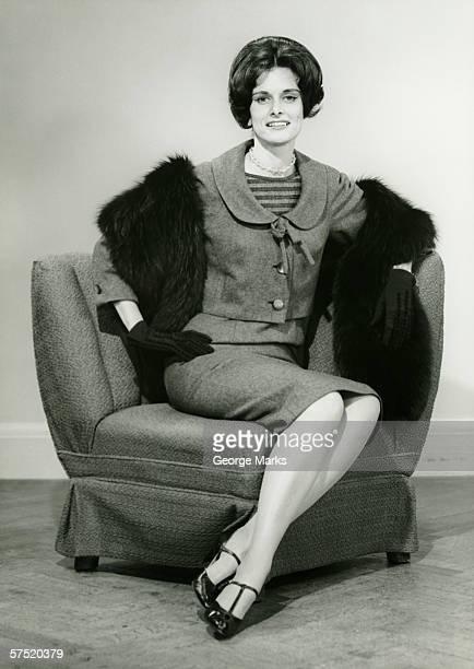 Elegant woman sitting on arm chair in studio, (B&W), portrait