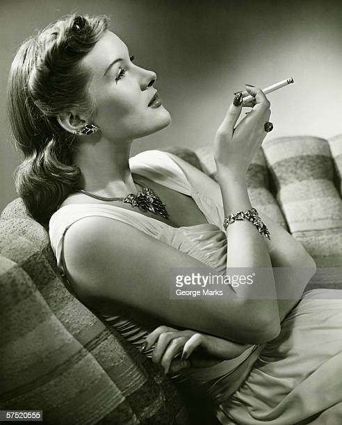エレガントなソファに座る女性、喫煙タバコ(b &w - 1930~1939年 ストックフォトと画像