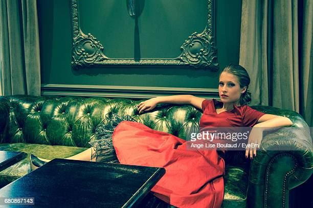 elegant woman sitting on retro sofa - leather dress stock pictures, royalty-free photos & images