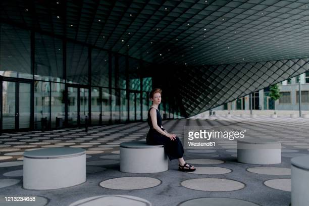 elegant woman sitting on round bench in futuristic architecture - berlin stock pictures, royalty-free photos & images