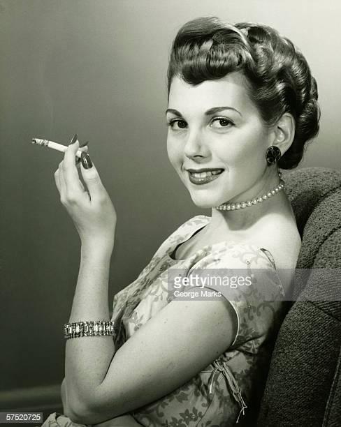elegant woman smoking cigarette, posing in studio, (b&w), portrait - beautiful women smoking cigarettes stock pictures, royalty-free photos & images