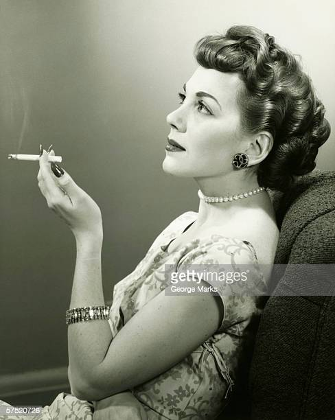 elegant woman smoking cigarette, posing in studio, (b&w), portrait - beautiful women smoking cigarettes stock photos and pictures