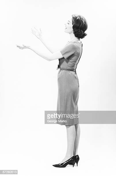 Elegant woman standing in studio, gesturing, (B&W)