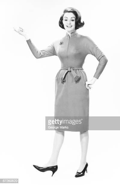 Elegant woman standing in studio, gesturing, (B&W), portrait