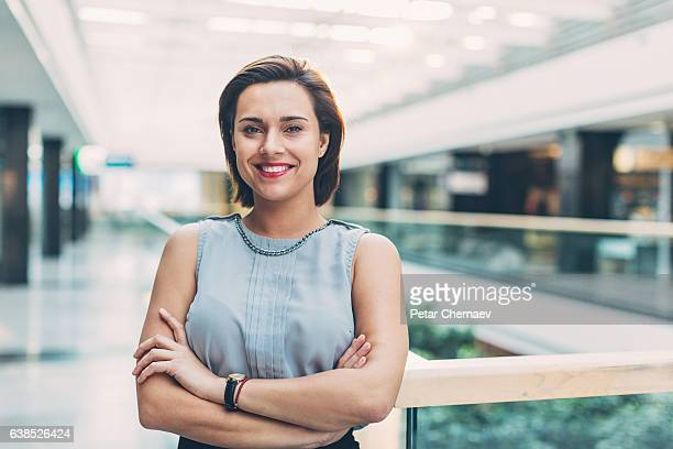 elegant woman standing inside of business building - employment law stock photos and pictures