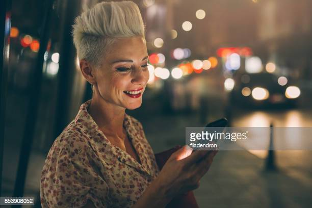 elegant woman texting at night - white hair stock photos and pictures