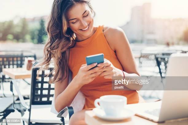Elegante Frau SMS im Freien im Sommer