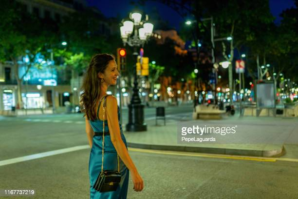 elegant woman walking at passeig de gràcia at night - satin dress stock pictures, royalty-free photos & images