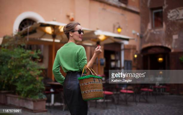 elegant woman walking on roman city street, holding basket - green skirt stock pictures, royalty-free photos & images