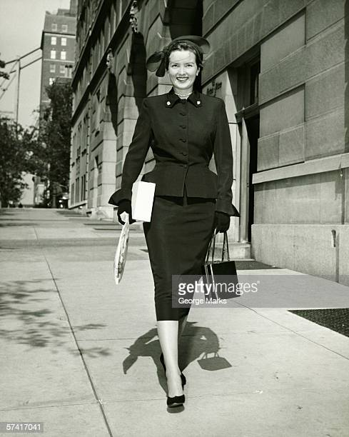 Elegant woman walking on sidewalk, (B&W)