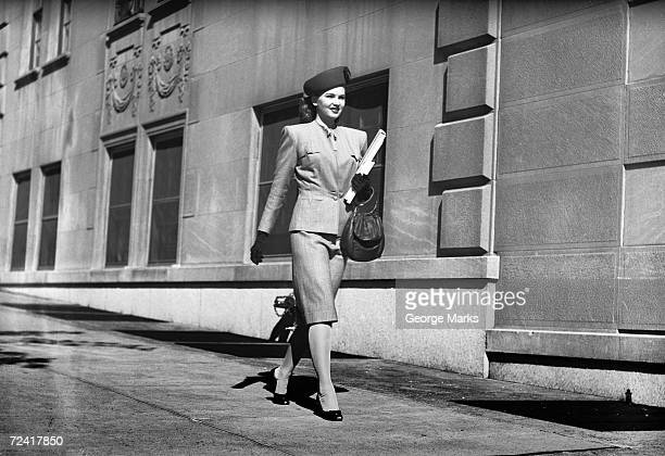 Elegant woman walking on sidewalk, (B&W)