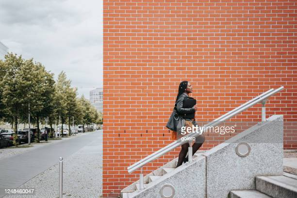 elegant woman walking up stairs in modern district in berlin - moving up stock pictures, royalty-free photos & images