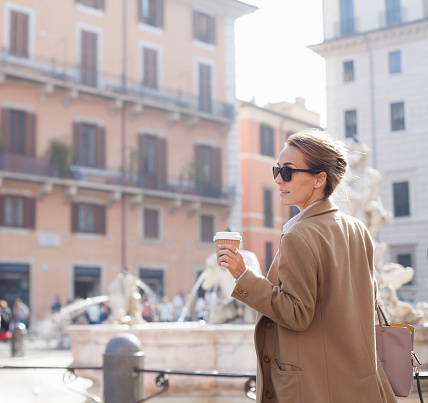 Elegant woman walking with takeaway coffee in sustainable coffee cup, Piazza Navona, Rome - gettyimageskorea