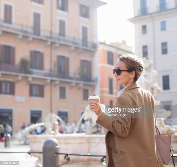 Elegant woman walking with takeaway coffee in sustainable coffee cup, Piazza Navona, Rome