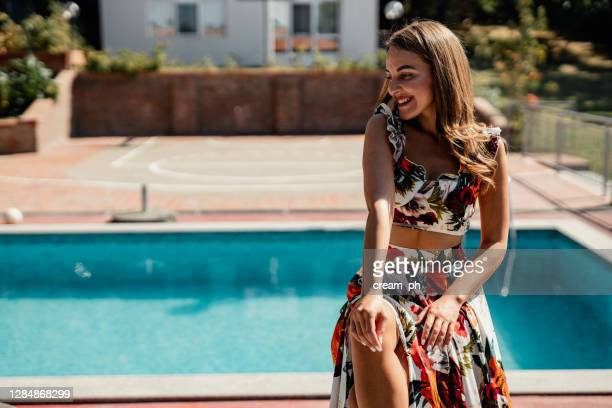 elegant woman wearing a fashionable floral long dress - sleeveless dress stock pictures, royalty-free photos & images