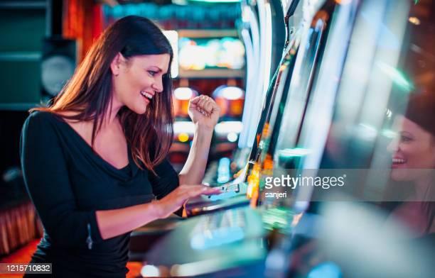 elegant woman winning on a slot machine - casino imagens e fotografias de stock